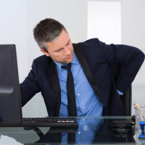 Portrait Of Businessman Suffering From Backpain In Office